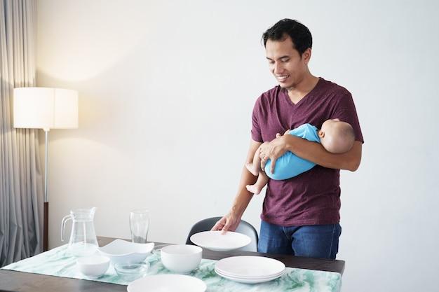 Portret van een alleenstaande vader die thuis klusjes doet terwijl hij zijn baby draagt