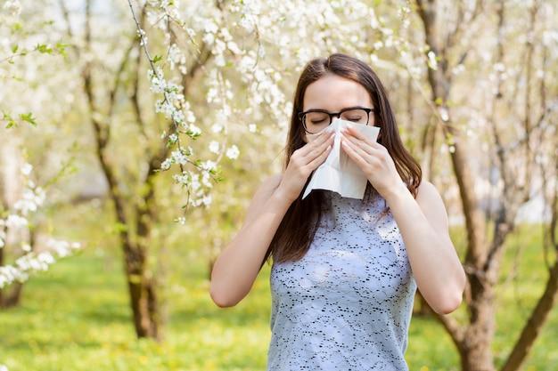 Portret van een allergisch jong meisje in het park dat wit servet houdt en wegens allergie op stuifmeel van bloeiende bomen niest
