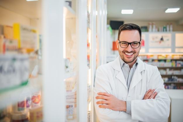 Portret van een apotheker bij drogisterij, glimlachend in de camera.