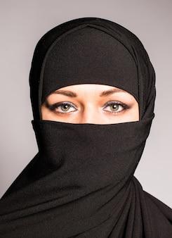 Portret van een arabische jonge vrouw met haar mooie blauwe ogen in traditionele islamitische doek niqab.