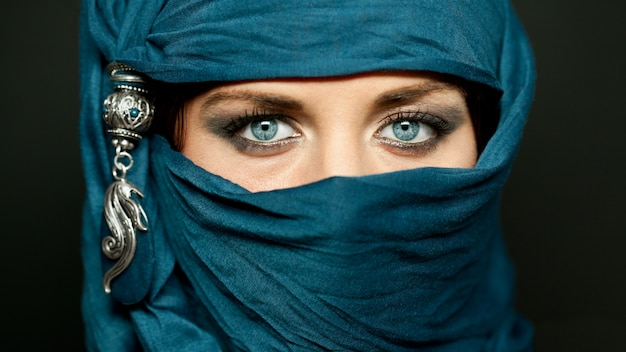 Portret van een arabische jonge vrouw met haar mooie blauwe ogen in traditionele islamitische doek niqab