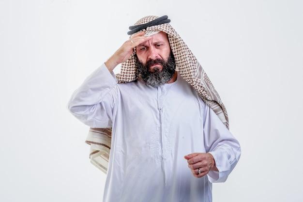 Portret van een arabische man die zich slecht voelt met fysieke druk op hoge temperatuur die de ogen gesloten houdt en het voorhoofd aanraakt met de palm geïsoleerd op een witte achtergrond