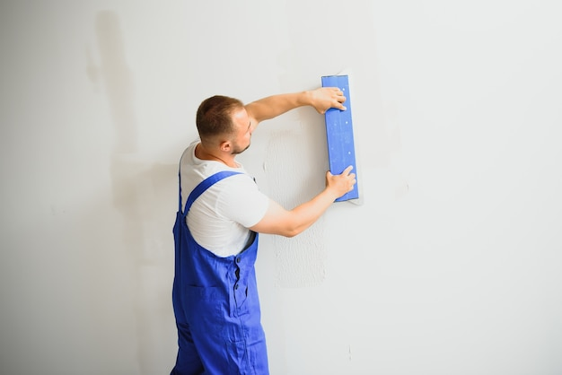 Portret van een arbeider in overall en met een plamuurmes in zijn handen tegen de gepleisterde muurachtergrond. reparatiewerk en bouwconcept