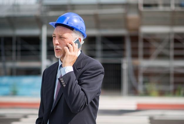 Portret van een architect die aan de telefoon aan zijn aannemer spreekt