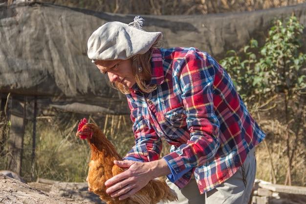 Portret van een argentijnse landarbeidersvrouw met een kip