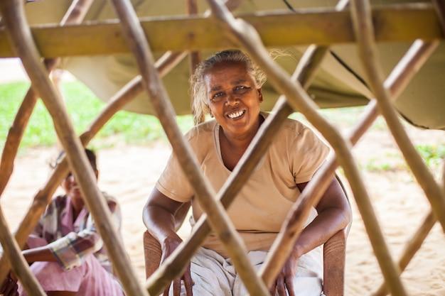 Portret van een arme, oudere indiase vrouw achter een hek in de vorm van een rooster