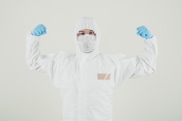 Portret van een arts die en spieren in masker, handschoenen en beschermend kostuum bevindt zich toont