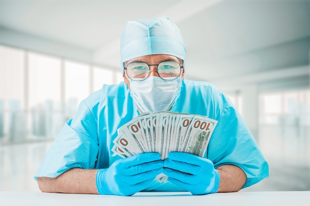 Portret van een arts die honderd dollarbiljetten houdt. hij kijkt naar de camera en lacht