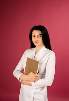 Portret van een arts in een medische witte jas met een blocnote op rood
