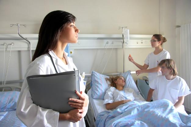 Portret van een arts met twee van haar collega's die met een patiënt op de achtergrond spreken