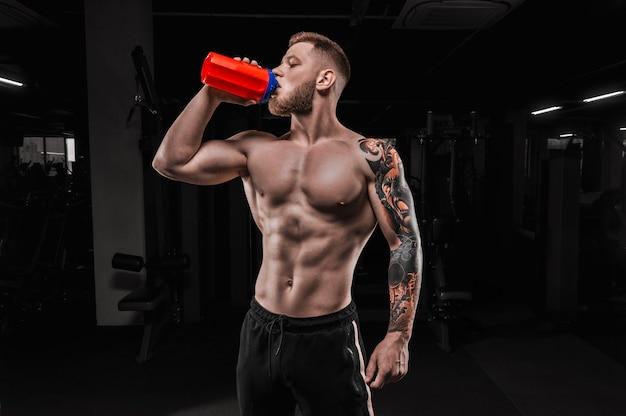 Portret van een atleet die drinkt uit een shaker in de sportschool. bodybuilding en fitness concept. gemengde media