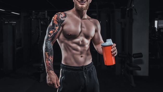 Portret van een atleet die met een shaker in de sportschool staat. bodybuilding en fitness concept. gemengde media