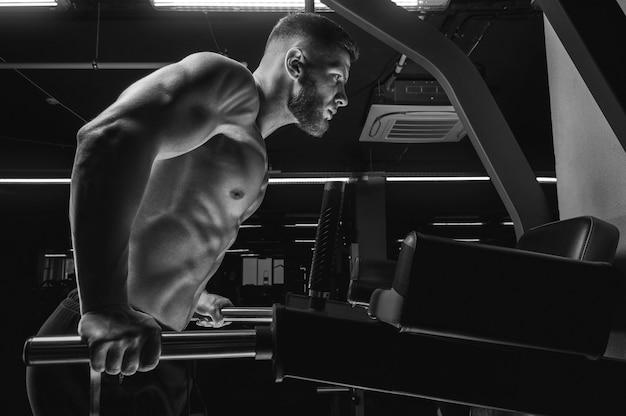 Portret van een atleet die push-ups doet op de ongelijke staven in de sportschool. bodybuilding en fitness concept. gemengde media