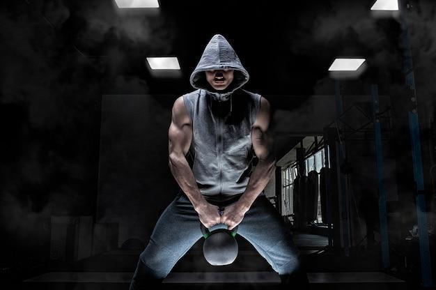 Portret van een atleet gehurkt met een kettlebell.
