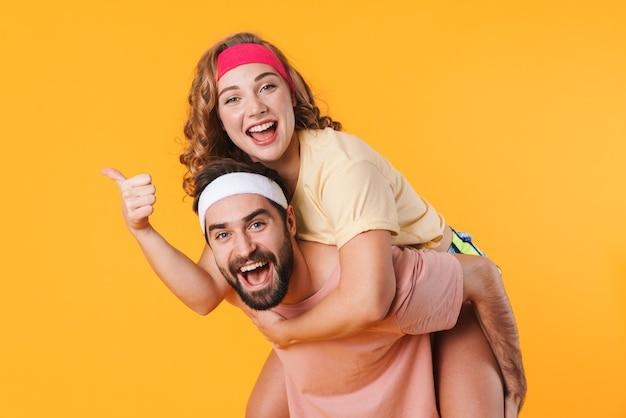 Portret van een atletisch jong gelukkig stel dat hoofdbanden draagt en glimlacht terwijl ze op de rug rijden, geïsoleerd over een gele muur