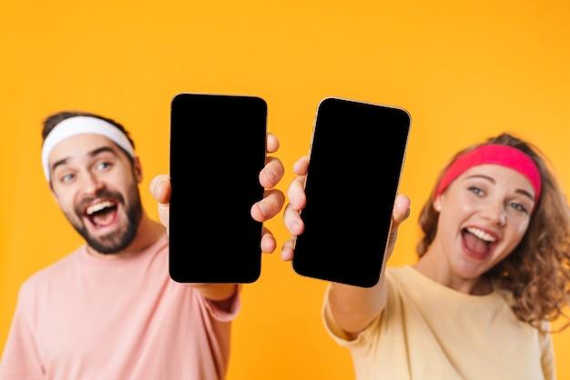 Portret van een atletisch jong stel met hoofdbanden die glimlachen en samen mobiele telefoons gebruiken, geïsoleerd over een gele muur