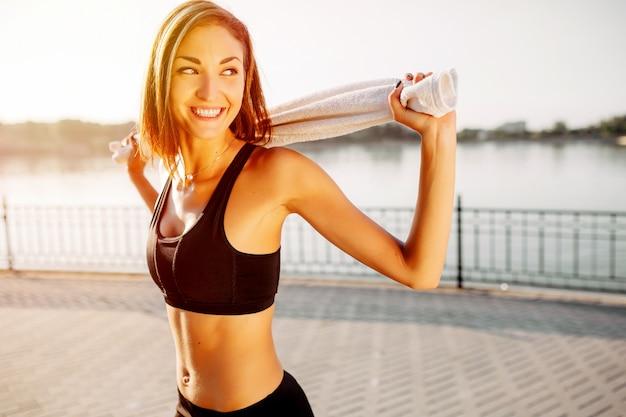 Portret van een atletisch meisje. mooi jong sportfitness model die klaar voor jogging in stadspark worden.