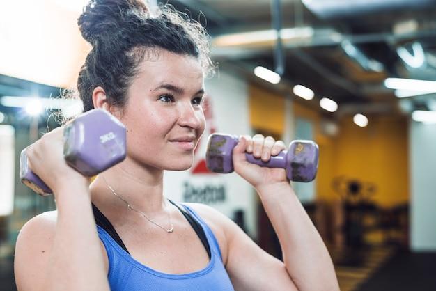 Portret van een atletische jonge vrouw die oefening met domoren doet