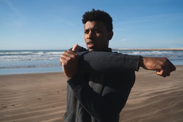 Portret van een atletische man die armen uitstrekt voor de training op het strand. sport en een gezonde levensstijl.