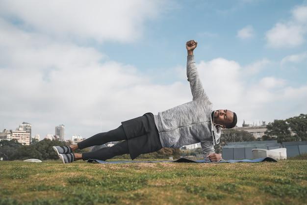 Portret van een atletische man die oefening in het park buiten doet. sport en een gezonde levensstijl concept.