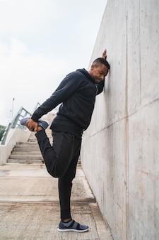 Portret van een atletische man die zich uitstrekt benen vóór oefening buitenshuis. sport en een gezonde levensstijl.