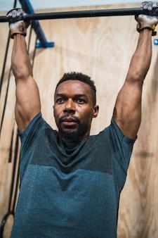 Portret van een atletische man doen pull-up oefening in de sportschool. sport en een gezonde levensstijl concept.