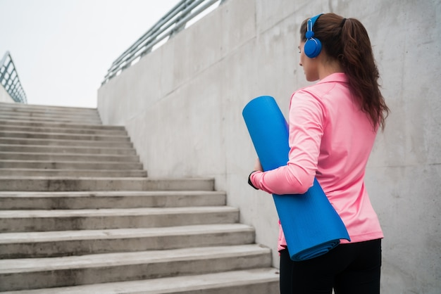 Portret van een atletische vrouw die een trainingsmat vasthoudt terwijl ze naar muziek luistert. sport en lifestyle concept.