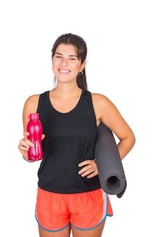 Portret van een atletische vrouw die een yogamat en een fles water houdt.