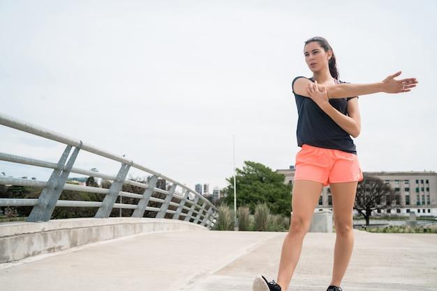 Portret van een atletische vrouw die haar armen vóór oefening in openlucht uitrekt. sport en een gezonde levensstijl.