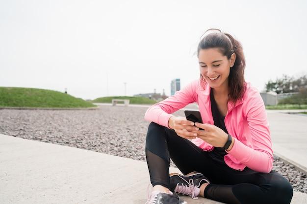 Portret van een atletische vrouw met behulp van haar mobiele telefoon tijdens een pauze van de training. sport en gezondheid levensstijl.