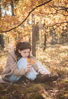 Portret van een attent en verdrietig meisje. herfst kleuren. levensstijl. herfst stemming. woud