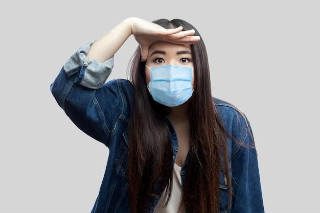Portret van een attente mooie brunette aziatische jonge vrouw met een chirurgisch medisch masker in een blauw spijkerjasje dat met de hand op het voorhoofd staat en kijkt. indoor studio opname, geïsoleerd op een grijze achtergrond.
