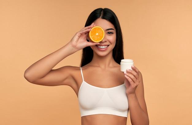 Portret van een aziatisch jong meisje met sinaasappel en vochtinbrengende gezichtscrème geïsoleerd op beige