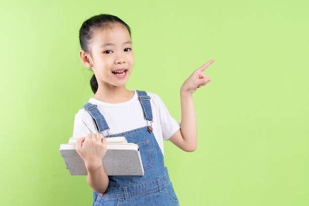 Portret van een aziatisch kind met een boek op een groene achtergrond