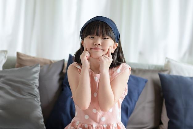 Portret van een aziatisch klein schattig meisje met een gelukkige charmante glimlach in de woonkamer thuis.
