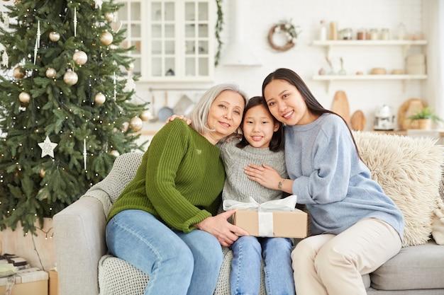 Portret van een aziatische familie van drie zittend op de bank met heden dat ze omarmen en lachend in de kamer