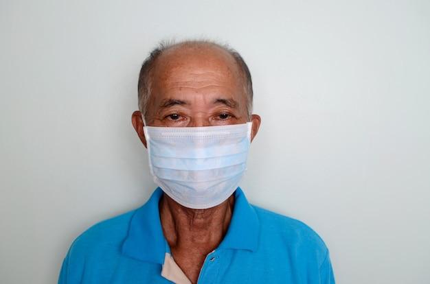 Portret van een aziatische hogere mens, 60 jaar oud die medisch masker draagt. een concept van het gevaar van coronavirus voor ouderen.