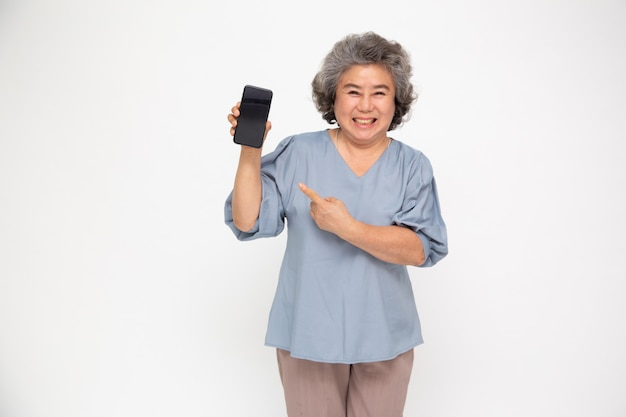 Portret van een aziatische hogere vrouw die of mobiele telefoontoepassing toont voorstelt en vinger richt op smartphone op hand die over witte muur wordt geïsoleerd, aziatisch thais rijp model