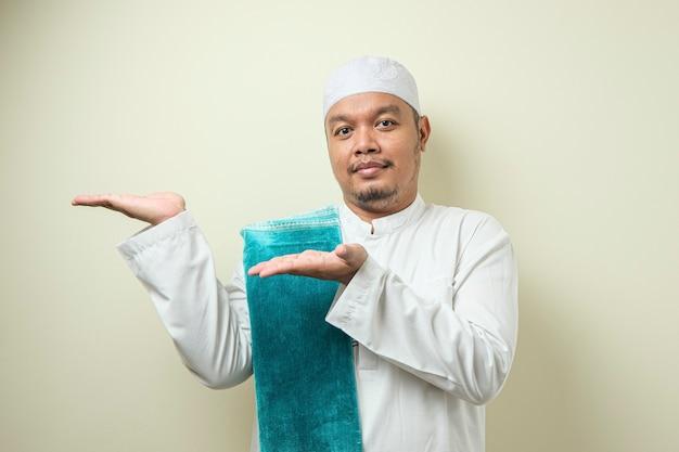 Portret van een aziatische jonge moslimman die lacht en wijst naar iets aan zijn zijde te presenteren
