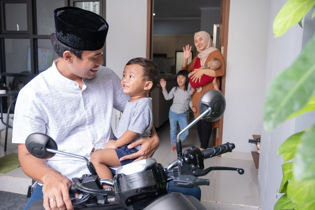 Portret van een aziatische man die afscheid neemt van zijn familiekind en -vrouw voordat hij op de motor vertrekt