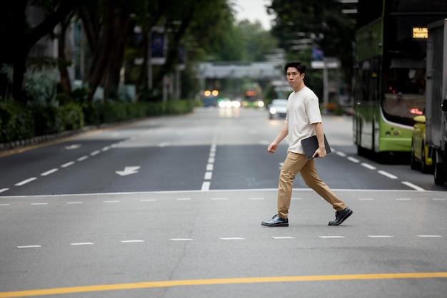 Portret van een aziatische man die de straat in de stad oversteekt terwijl hij een laptop vasthoudt