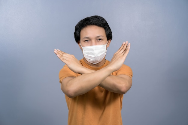 Portret van een aziatische man die een chirurgisch gezichtsmasker draagt en geen actie zegt tegen een coronavirusinfectie