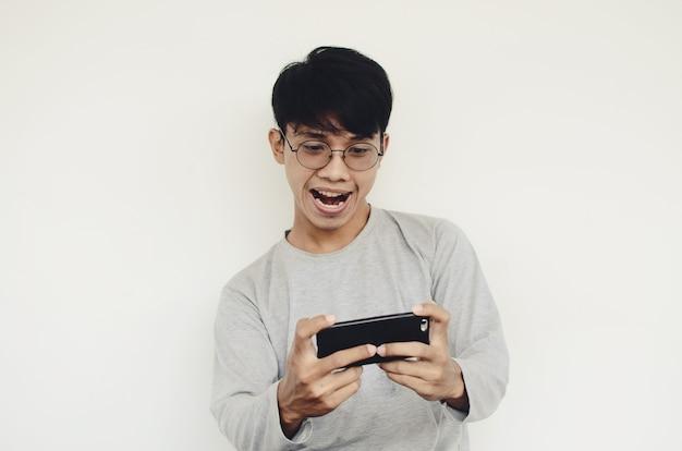 Portret van een aziatische man die spelletjes speelt op zijn mobiel