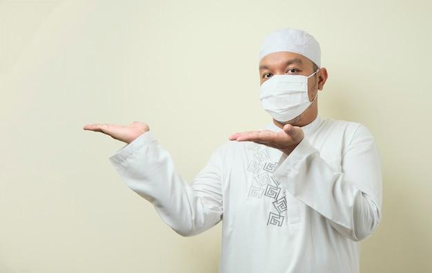 Portret van een aziatische moslimman die een masker draagt en wijst naar iets aan zijn zijde te presenteren