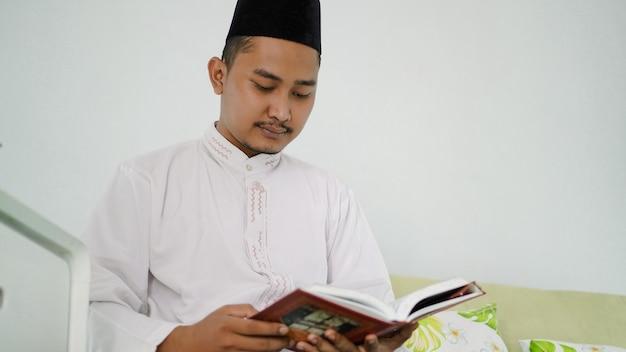 Portret van een aziatische moslimman die thuis de heilige koran leest