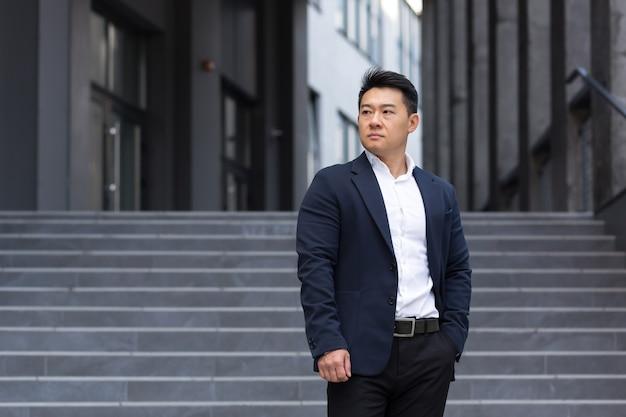 Portret van een aziatische serieuze zakenman in de buurt van kantoor in een zelfverzekerde verkoopmanager van een makelaar