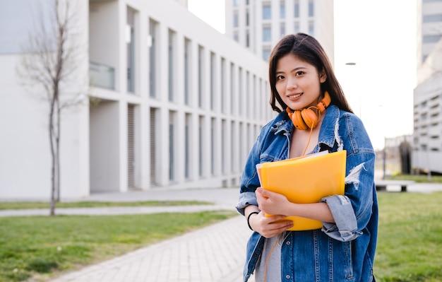 Portret van een aziatische student die zich buiten op het onderwijsconcept van de universiteitscampus bevindt