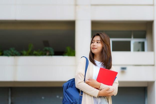 Portret van een aziatische studente die een rugzak draagt en zich in een schoolgang bij campus bevindt.