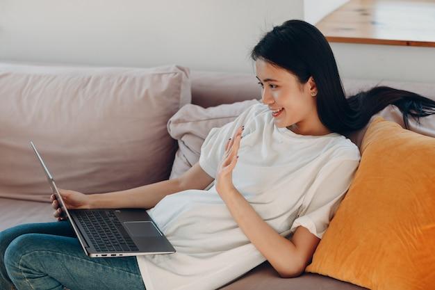 Portret van een aziatische vrouw die geniet van het gebruik van een laptop in de woonkamer van het appartement videogesprek vlogger webinar stream concept