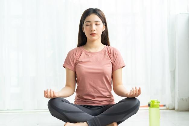 Portret van een aziatische vrouw die thuis yoga beoefent